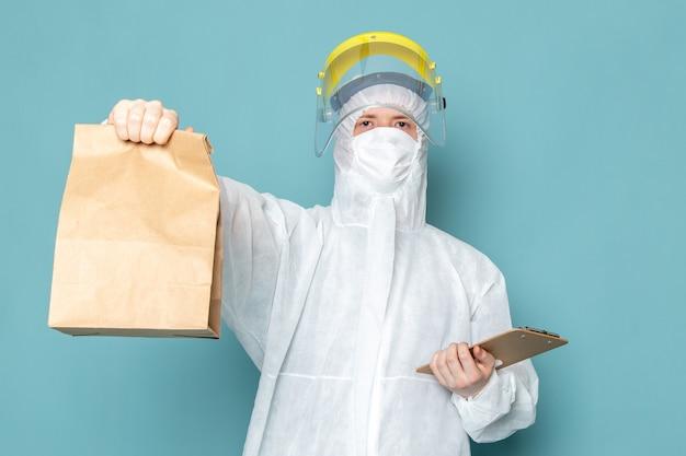 白の特別なスーツと青い壁のスーツを保持している黄色の特別なヘルメットの正面の若い男性スーツの危険な特別な装置の色