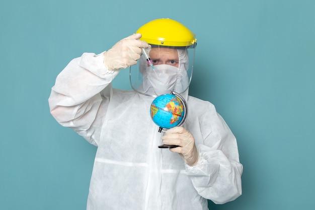 白い特別なスーツと青い壁の男に小さな地球を注入する黄色の特別なヘルメットの正面の若い男性スーツ危険特別装備色