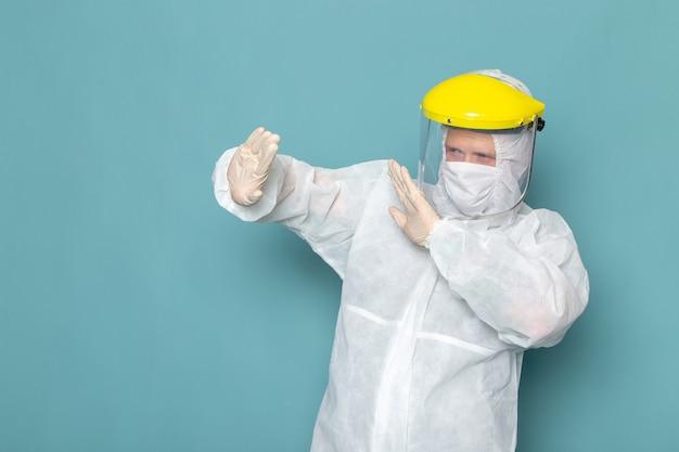 白の特別なスーツと青い壁の男の距離を保つ黄色の特別なヘルメットの正面図の若い男性のスーツの特別な装備の色