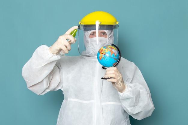 Вид спереди молодой мужчина в белом специальном костюме и желтом специальном шлеме, использующий спрей на синей стене, мужчина подходит для опасного специального оборудования цвета
