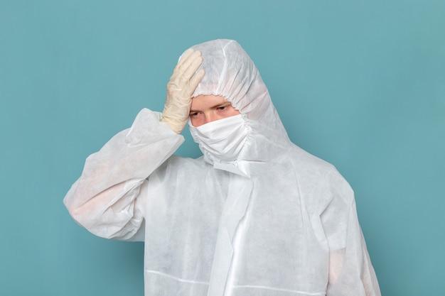 青い壁の男のスーツの危険な特別な機器の色に頭痛を持っている白い特別なスーツの正面図の若い男性