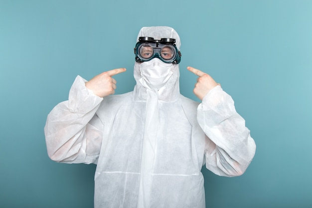 青い壁の男の白い特別なスーツの正面の若い男性のスーツの危険の特別な装置の色