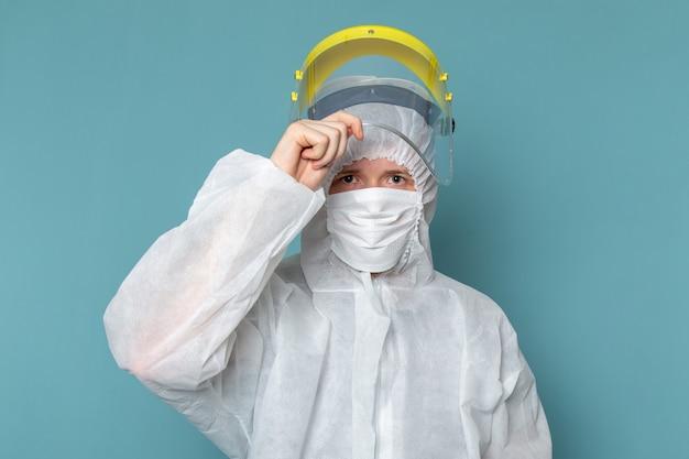 Вид спереди молодой мужчина в белом специальном костюме, снимающий специальную маску на голове на синей стене, мужской костюм опасного цвета специального оборудования