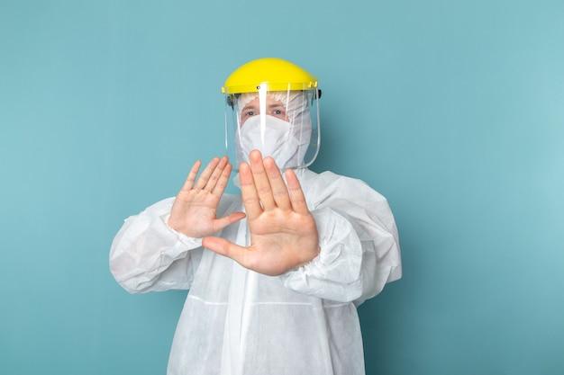 水色の壁に特別なヘッドマスクを身に着けている白い特別なスーツの正面若い男性