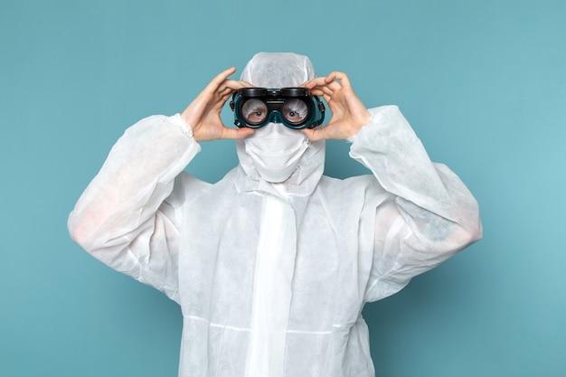 Вид спереди молодой мужчина в белом специальном костюме, одетый в специальные солнцезащитные очки на синей стене, мужской костюм опасного цвета специального оборудования