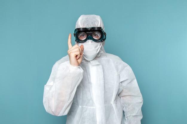 青い壁を脅かす特別なサングラスを身に着けている白い特別なスーツを着た若い男性の正面男性のスーツの危険特別装備色