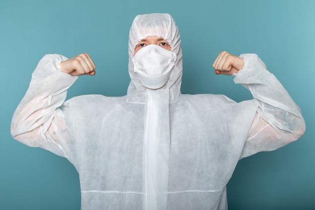 正面図の若い男性は白い特別なスーツを着て、青い壁の男性の防護マスクを曲げて、防護マスクを着用します。