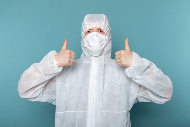 青い壁の男の滅菌の防護マスクを身に着けている白い特別なスーツの正面図の若い男性のスーツの特別な機器の色の危険