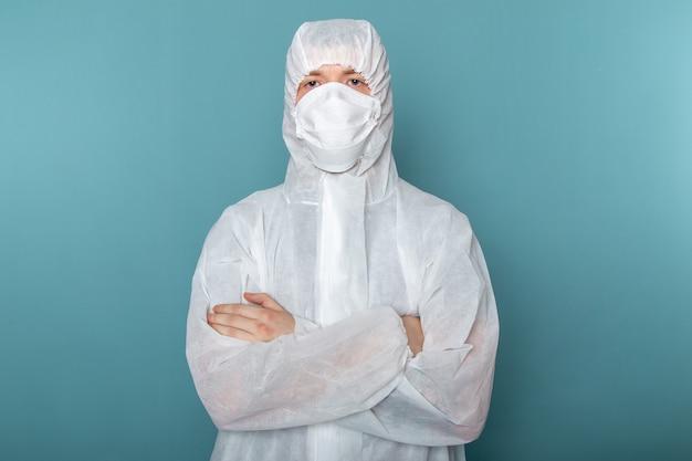 青い壁の男のスーツの危険な特別な機器の色でポーズをとって滅菌防護マスクを身に着けている白い特別なスーツの正面図の若い男性