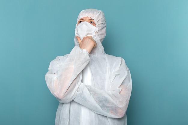 青い壁の男のスーツの危険な特別な機器の色を考えて滅菌防護マスクを身に着けている白い特別なスーツの正面図の若い男性