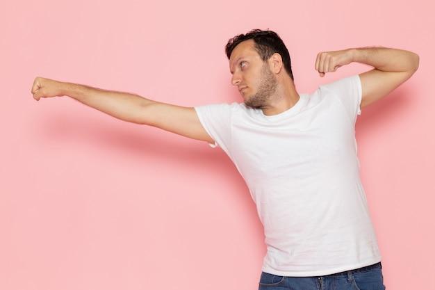 Молодой мужчина в белой футболке и синих джинсах, вид спереди, бьет ногой по розовому столу.