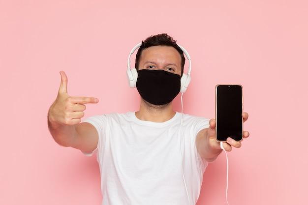 ピンクのデスクマン色感情ポーズでイヤホンを介して音楽を聴く白いtシャツブラックマスクの正面図の若い男性