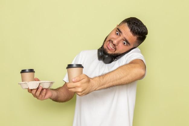 電話で話しながらコーヒーカップを保持している白いtシャツの正面の若い男性