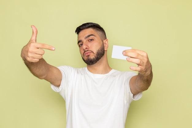 白いカードを保持している白いtシャツの正面の若い男性