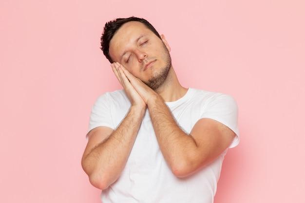 Молодой мужчина в белой футболке, вид спереди, позирует со сладким спящим выражением лица