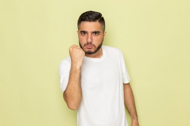 Молодой мужчина в белой футболке, вид спереди, показывает его кулак