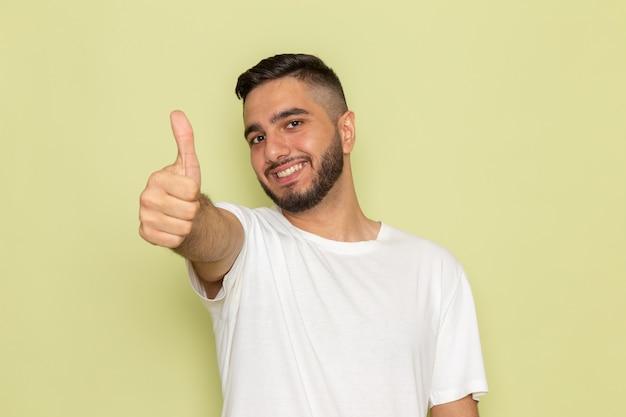Молодой мужчина в белой футболке, улыбаясь, позирует с похожим знаком