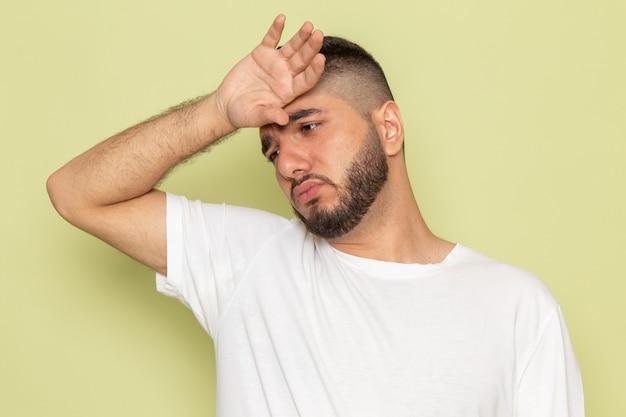 Молодой мужчина в белой футболке с усталым выражением лица, вид спереди