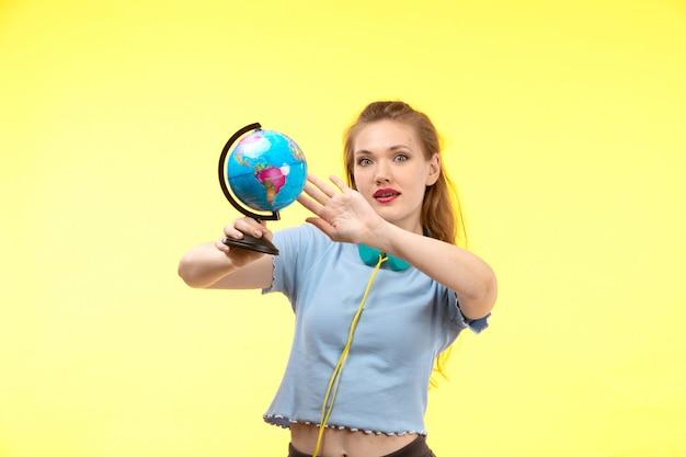 Вид спереди молодая современная женщина в синей рубашке черные брюки в разноцветных наушниках держит маленький глобус