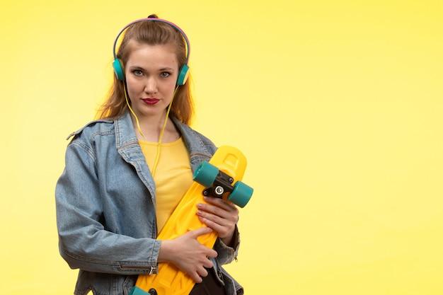 Вид спереди молодая современная женщина в желтой рубашке черные брюки и джинсовая куртка держит скейтборд с цветными наушниками позирует