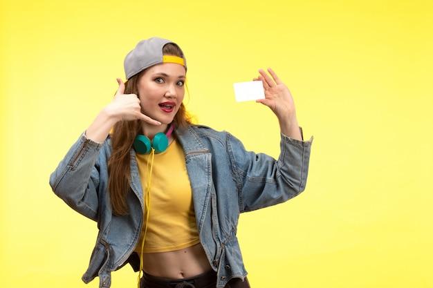 Вид спереди молодая современная женщина в желтой рубашке черных брюк и джинсовой куртке с цветными наушниками держит белую карточную позу