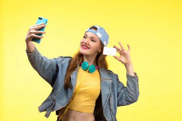 Вид спереди молодой современной женщины в желтой рубашке, черных брюках и джинсовой куртке с цветными наушниками, держа белую карточку с помощью телефона, принимая селфи позирует