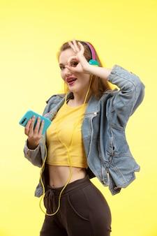 음악을 듣고 컬러 이어폰과 노란색 셔츠 검은 바지와 진 코트의 전면보기 젊은 현대 여성