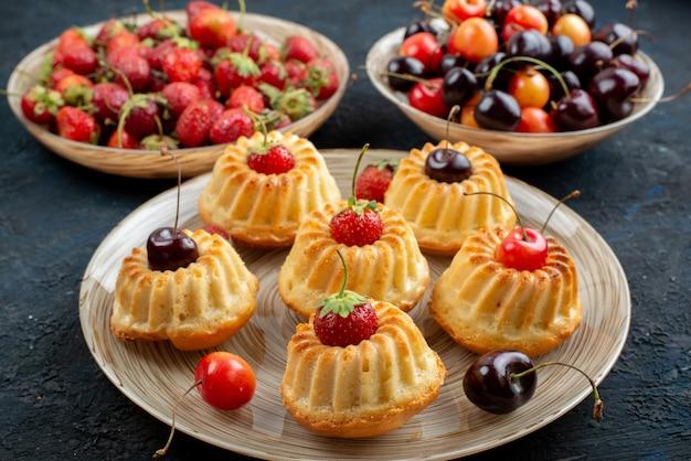 Вкусное печенье с красной клубникой и вишней на тарелке на темном столе, вид спереди