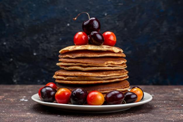 Вкусные блины с вишней на белой тарелке на темном столе, фруктовый блин, вид спереди