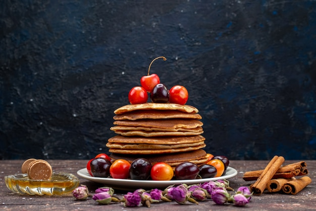 Вкусные блины с вишней на белой тарелке с корицей на темном столе, фруктовый блин, вид спереди