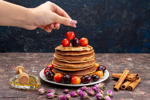 Вид спереди вкусные блины с вишней внутри белой тарелки с цветами и корицей на темном фоне фруктовые блины