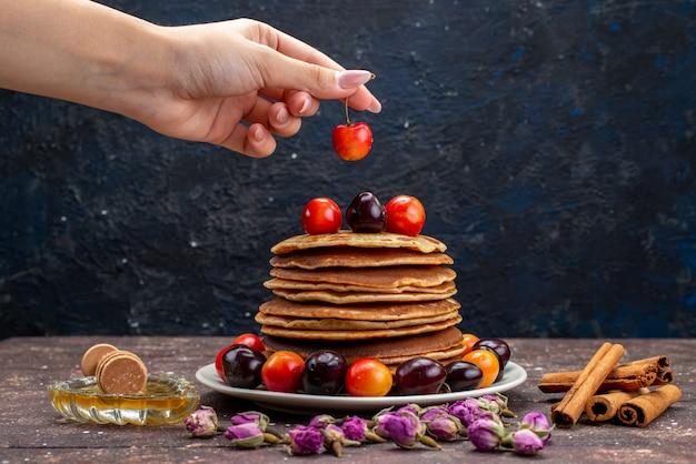 Вкусные блины с вишней на белой тарелке с цветами и корицей на темном столе, фруктовый блин, вид спереди
