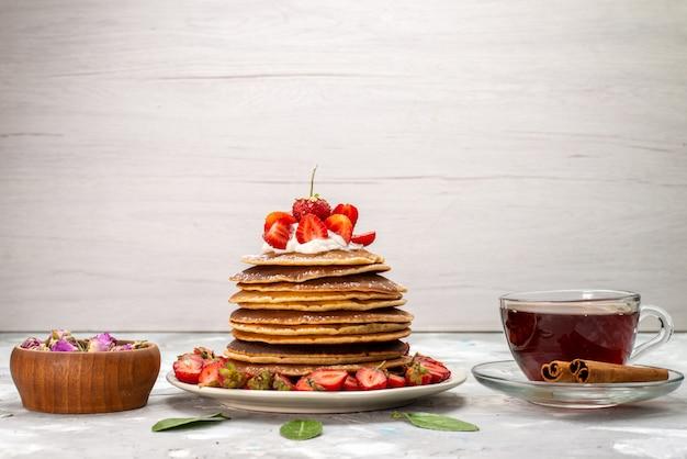 Вкусные круглые блины со сливочным чаем и красной клубникой на светлом столе, фруктовый торт, вид спереди