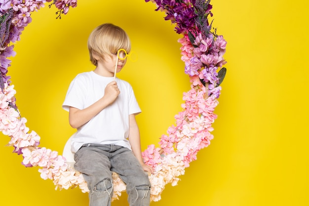 Передняя симпатичная блондинка в белой футболке, сидящая на цветке, стоит на желтом полу