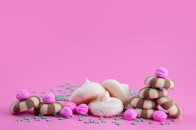 ピンクの机のメレンゲ、クッキービスケットキャンディーカラーと一緒にチョコレートクッキー