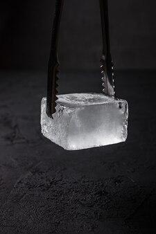 バーテンダーアイストング、暗い背景のクーペガラス用の冷凍角氷