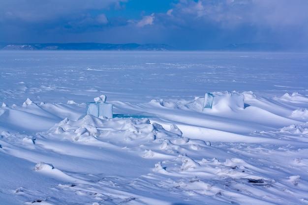 Замерзшее озеро со сугробами и вырезанными на снегу кусочками льда