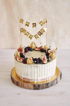 Фруктовый торт ко дню рождения с топпером на день рождения, фруктами сверху и белой каплей на бежевом фоне