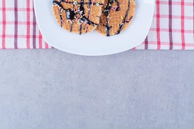ふりかけとクリームが入った丸い血色の良いワッフルのフライパン。