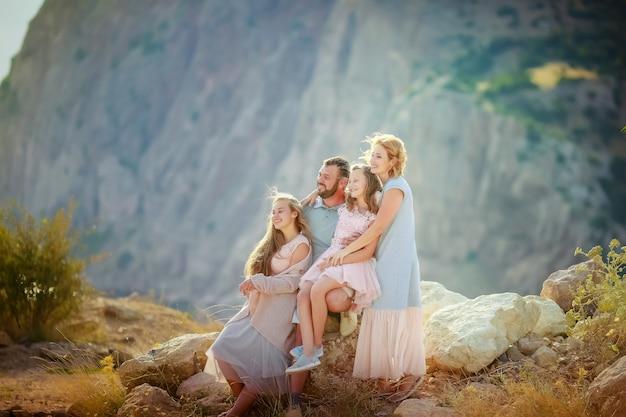 Полная семья из четырех мам пап и двух дочерей вместе на вершине горы над морем