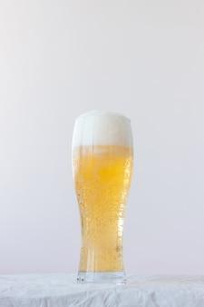 거품과 거품이 있는 가벼운 맥주 한 잔이 흰색 배경에 서 있습니다.