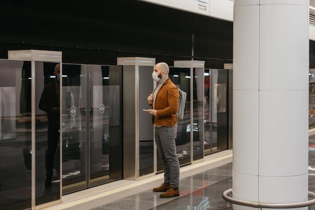 フェイスマスクをした男性の全身写真が、地下鉄のホームで電車を待っている間、スマートフォンを持っています。サージカルマスクのハゲ男が社会的距離を保っています。