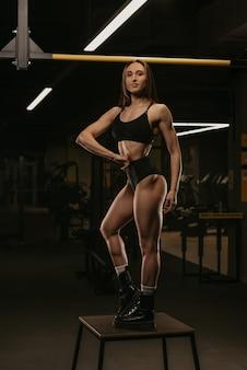 ジムでの背中のトレーニングの後、腰に手を当ててポーズをとっているスポーティな女性の全身写真。筋肉質のブルネットの女の子は、黒のトップとハイウエストのショートパンツを着ています。