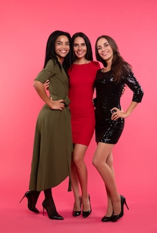 パーティードレスを着てポーズをとる3人の魅力的な女性の全身写真。お互いの腰を抱きしめ、大きく笑っている。