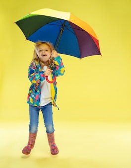 노란색 스튜디오 벽에 무지개 색상의 우산을 들고 비옷에 밝은 유행 소녀의 전체 길이 초상화