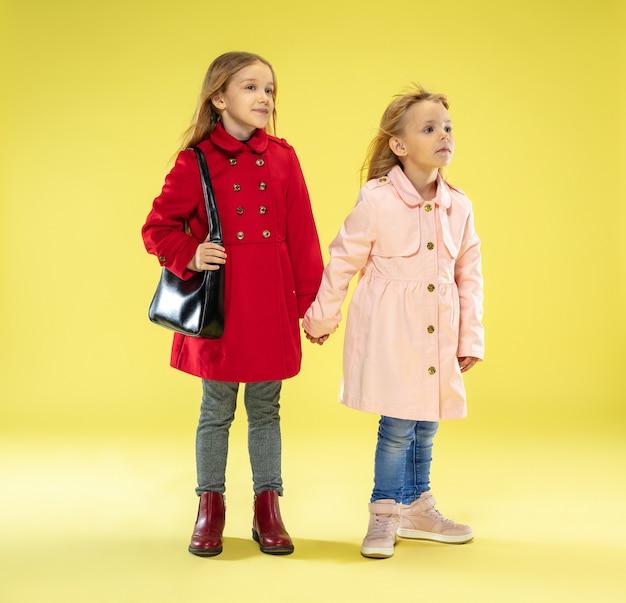 黄色のスタジオの壁に黒いバッグを持っているレインコートを着た明るくファッショナブルな女の子の全身像