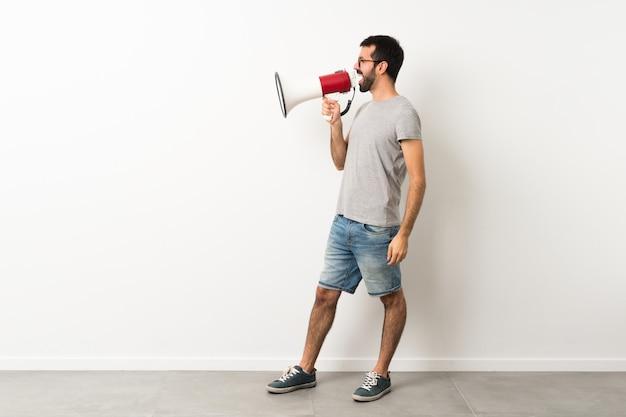 Полнометражный снимок красавца с бородой, кричащего через мегафон