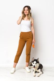 彼女の犬と一緒に完全な長さの若いきれいな女性