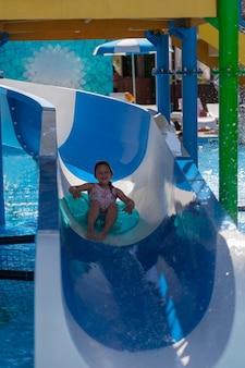 ピンクの水着を着た全身の幸せな女の子がウォータースライドから膨らませて円に乗る