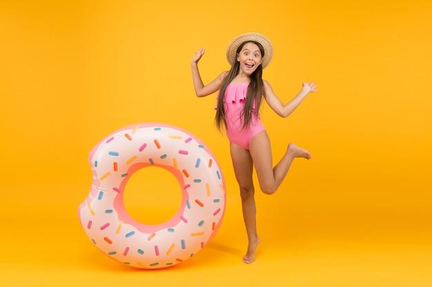 재미있는 액세서리 행복한 어린 시절 어린 소녀는 밀짚 모자와 수영복을 입고 노란색으로 웃는 아이
